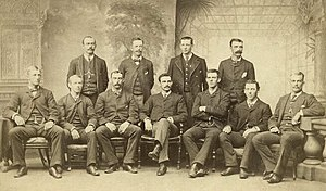 Baseball players are posing for a photograph, four men standing, seven men sitting on chairs.