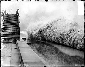 Great Lakes Storm of 1913 - A wave breaking on the shore of Lake Michigan  in Chicago while a man watches from a bridge