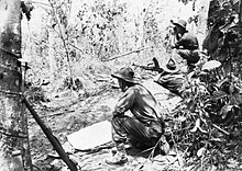 Black and white photo of a man wearing military uniform armed with a large gun lying down and aiming the weapon into dense bushland. Two other men in military uniform are crouched on either side of the prone man.