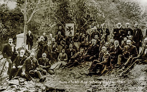 20th Maine Volunteer Infantry Regiment - 1889 reunion veterans of the 20th Maine Volunteer Infantry, at Gettysburg, Pennsylvania. General Joshua L. Chamberlain, the officer who commanded them in battle, seated at center right, bracketed by the Maltese Cross banner of the V Corps (5th) and the unit's regimental flag. Left is a monument to the unit recently erected by its veterans. Black and white photograph
