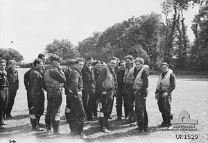 Black-and-white photo of a group of young men wearing military uniforms and life preservers standing in a field edged with trees