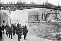 Soldiers carrying kit-bags approaching the photographer, while walking on an embankment next to a river with steel girder bridge in the background.