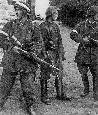 "Battalion Zośka - Battalion Zośka soldiers during the Warsaw Uprising 5 August 1944 in Gęsiówka. The men are dressed in stolen German uniforms and armed with confiscated German weapons. From left: Wojciech Omyła ""Wojtek"", Juliusz Bogdan Deczkowski ""Laudański"" and Tadeusz Milewski ""Ćwik"". Milewski was killed on the same day. Omyla was killed several days later on 8 August 1944."