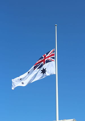 Half-mast - The Australian White Ensign flying at half-mast. In accordance with British tradition, the flag is flying only one flag's width below the top of the pole.