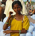 A girl selling plastic containers for carrying Ganges water, Haridwar (cropped).jpg