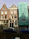 foto van Huis met gevel op houten pui, de tweede verdieping later vernieuwd en onder rechte lijst gebracht