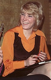 A blonde woman wearing an orange blouse and a black vest