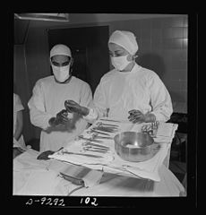 Assisting at an operation, a nurse hands a threaded needle 8b08199v.jpg