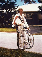 Man in his forties, standing in front of a house and holding a bicycle and helmet.  He is smiling and wearing a red, white, and blue jumpsuit.