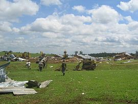 A destroyed poultry farm with debris strewn across a field