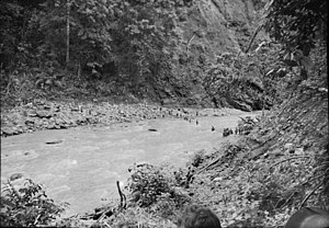 Battle of Rabaul (1942) - Late January 1942. Australian soldiers (right centre) retreating from Rabaul cross the Warangoi/Adler River in the Bainings Mountains, on the eastern side of Gazelle Peninsula. Photographer: Sgt L. I. H. (Les) Robbins.