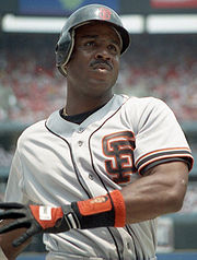 "An African-American man looks just right of the camera. His helmet and white jersey both have an orange ""S"" over ""F"" logo on them. The man's left arm is crossed over his body and his right is out of the picture. There is a black and orange glove on his left hand."