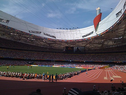 Inside Beijing National Stadium during the Games. Olympic cauldron in background. Beijing Birds Nest Olympics track .jpg