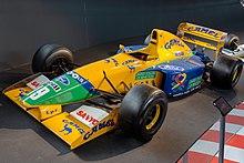 Photo d'une monoplace jaune, bleue et verte exposée dans un musée