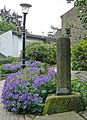 Bent lampost, pillar and purple flowers (4746866542).jpg