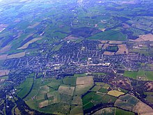 aerial picture of the town surrounded by green fields.