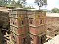 bâtiment aux facades roses percées de fenêtres à cintre ogival, dans une excavation,