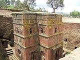 byggnad med rosa fasader genomborrad med välvda välvda fönster, i en utgrävning.