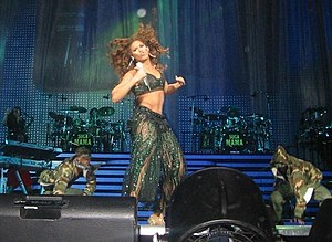 Beyoncé -  alt=A woman, flanked by two male dancers, holds a microphone in one hand as she dances