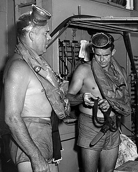 This is a photo of Commander George F. Bond and Chief Engineman Cyril Tuckfield after safely completing a 302 foot buoyant ascent in 52 seconds from the forward escape trunk of  USS Archerfish bottomed at 322 feet.