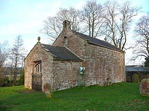 A small bare stone building seen from an angle, a lower section with a doorway at the front, and a larger, higher section with a bellcote at the back