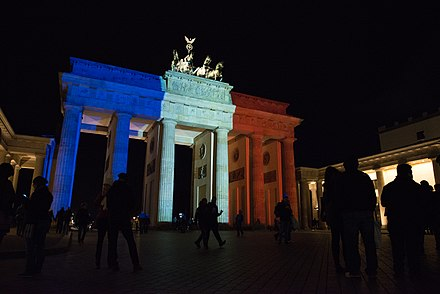 The Brandenburg Gate in Berlin was one of many world landmarks illuminated in the French flag colors after the November 2015 Paris attacks. Brandenburg Gate in French flag colours after Paris attack (23028317551).jpg