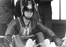 A man wearing a skin-tight cold-protecting jumpsuit, gloves, and a full-face helmet with a lifted visor. He is sitted on a sled and there are people behind him.