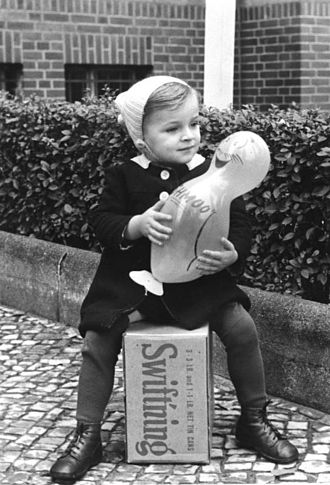 Shmoo - A child in West Berlin holding a toy Shmoo and sitting on a CARE Package (October 1948)