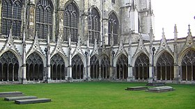 exterior of Gothic cathedral with lawn bounded by single-storey cloister