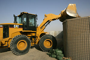 An Iraqi soldier uses a Caterpillar loader to ...