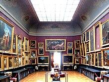 Grande salle aux tentures rouges couvertes de tableaux de grande dimension avec une porte d'entrée au fond
