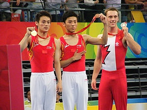 2008 Summer Olympics medal table - Left to right: Lu Chunlong (gold), Dong Dong (bronze), both from China, and Jason Burnett from Canada (silver) won medals in gymnastics – Men's trampoline