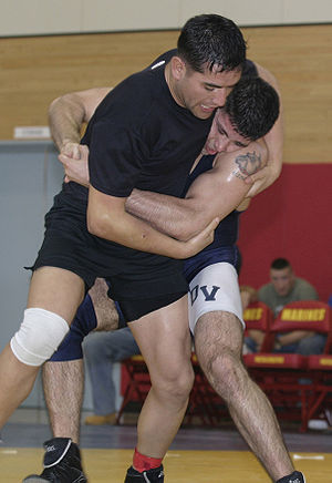 Two wrestlers clinching with one getting the back.