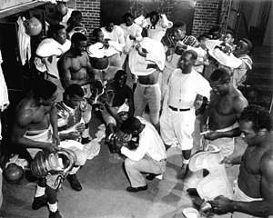 Jake Gaither - Coach Jake Gaither (standing, middle, white shirt with whistle) in the locker room with his Florida Agricultural and Mechanical University (FAMU) football team: Tallahassee, Florida, 1953