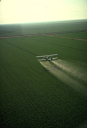 Pesticide - A crop-duster spraying pesticide on a field