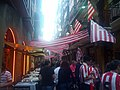 Crowded street with red and white flags above (19034708876).jpg
