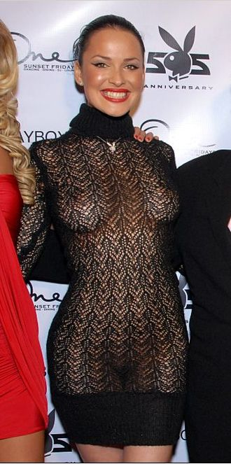 Fetish fashion - Playboy Playmate Dasha Astafieva wearing a see-through fishnet dress without underwear, poses for photographers at a Playboy party in USA, 2008.