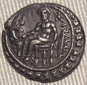 Baaltars - Silver coin of Datames (r. 385-362 BCE) with the God Baaltars on a throne, seated left, torsos facing, holding grapes, grain ear, and eagle in right hand, scepter in left hand, surrounded by the city walls. Cabinet des Médailles.