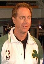 A man, wearing white and green jacket with the NBA logo and green shamrock on the front, is standing and looking to the front.