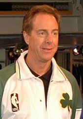 Portrait photograph of white man wearing white and green top