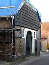 foto van Pakhuis in vakwerkbouw met gemetselde vullingen en natuurstenen plint
