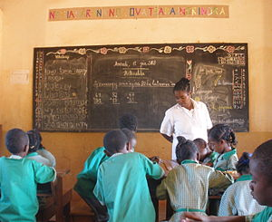 Malagasy children in green school uniforms working in groups as a teacher in white looks on