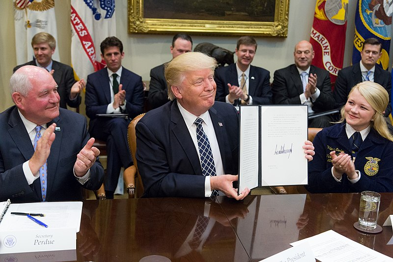 Donald Trump displays the signed Executive Order promoting Agriculture and Rural Prosperity