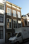 foto van Hoekpand Heer Heymansuysstraat. Lijstgevel met gesneden consoles (Lodewijk XV) en verkropte kroonlijst. Empire schuiframen. In het souterrain getoogde poort