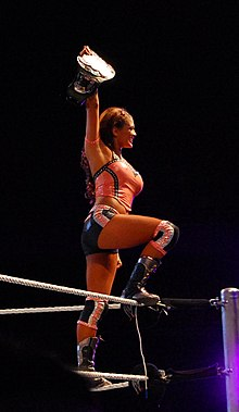 A dark-haired woman standing on the turnbuckle of a wrestling ring, with one foot on the red ring ropes. She is wearing an orange crop top with dark shorts and dark-coloured wrestling boots. Her right hand is holding a wrestling championship in the air.