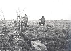 Mercenarios deJulio Popperdisparando. En el suelo se observa el cadáver de un selknam.