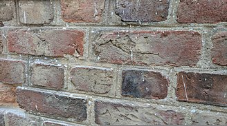 Lime mortar - The large flakes of oyster shell are a signal that this is a faux shell mortar. In fact it was a very hard Portland replacement which luckily had not done much harm to the brick.