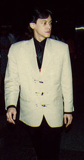 An Indonesian man, standing stiffly, wearing a white jacket