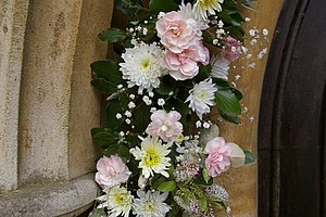 English: Flowers round church door at St John ...
