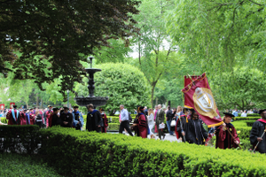 Students and faculty in commencement garb walking down pathway among greenery.